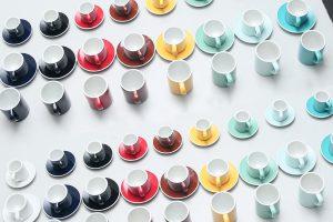 Gekleurde koffiekopjes op rij